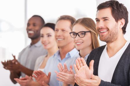 manos aplaudiendo: Aplaudiendo a las innovaciones de las empresas. Grupo de gente de negocios alegre aplaudiendo a alguien mientras está de pie en una fila