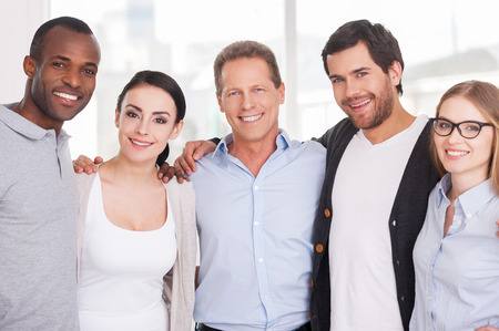 We are strong creative team! Group of cheerful business people in casual wear standing close to each other and looking at camera