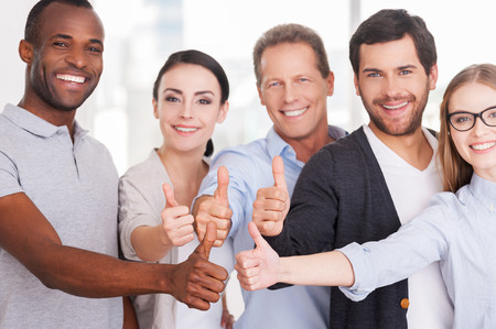 thumbs up group: Happy business team. Group of cheerful business people in casual wear standing close to each other and showing their thumbs up