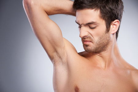 Portrait of young shirtless man looking at his armpit and grimacing while standing isolated on grey background photo