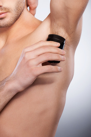 Cropped image of young shirtless man using dry deodorant while standing isolated on grey background photo