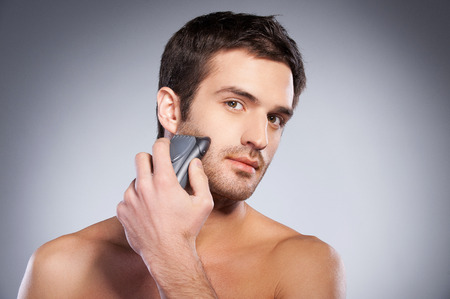 Handsome young man shaving his face with electric shaver and looking at camera while standing isolated on grey background photo