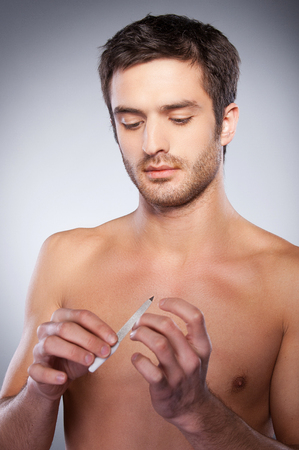 Handsome young shirtless man polishing his nails while standing isolated on grey background photo
