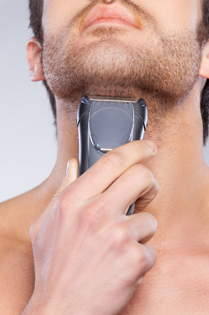 Close up of young man shaving his face with electric shaver while standing against grey background photo