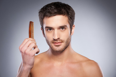 Handsome young shirtless man holding a comb and looking at camera while standing against grey background photo