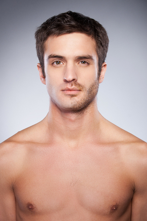 Half shaved. Handsome young man with half shaved face looking at camera while standing against grey background photo