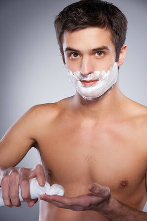 Handsome young shirtless man applying shaving cream at his face and looking at camera while standing isolated on grey background photo