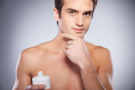 Handsome young shirtless man applying cream at his face and looking at camera while standing against grey background photo