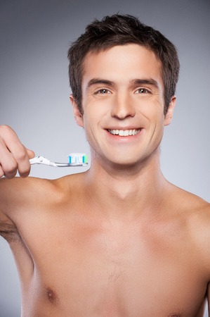 Cropped image of handsome young shirtless man holding a toothbrush with toothpaste and smiling while standing against grey background photo