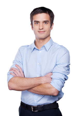 Handsome young man in blue shirt looking at camera and keeping arms crossed while standing isolated on white