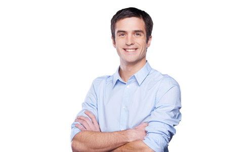 Portrait of handsome young man in blue shirt looking at camera and keeping arms crossed while standing isolated on white