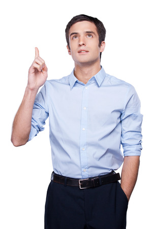 Thoughtful young man in blue shirt gesturing and looking away while standing isolated on white photo