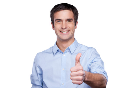 Portrait of handsome young man in blue shirt showing his thumb up and smiling while standing isolated on white photo