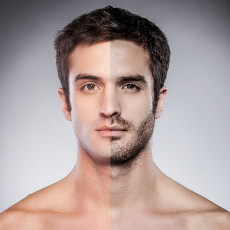 men sex: Handsome young man with half shaved face looking at camera while standing against grey background