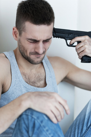 Suicide. Depressed young man sitting on the floor and holding gun near his head photo