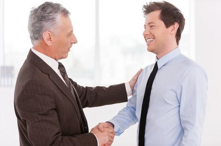Zakelijke partners. Twee vrolijke zakelijke mannen schudden handen en kijken naar elkaar