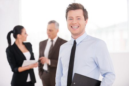 Confident young businessman. Cheerful young man in formalwear holding clipboard and smiling while his colleagues talking on background photo