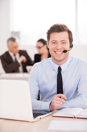 Always ready to help. Handsome young man in headset looking at camera and smiling while people working  photo