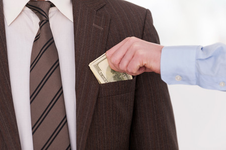 bribing: Bribing. Close-up of businessman putting money to the pocket of another man in formalwear