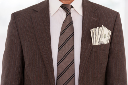 Corrupted businessman. Close-up of businessman in formalwear with money stretching out of his pocket  photo