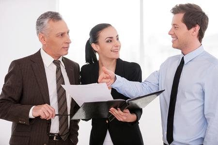 buen trato: Creo que es un buen negocio. Tres hombres de negocios conf�a en discutir algo, mientras que la mujer lleva a cabo documentos