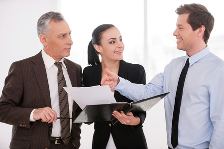 I think it is a good deal. Three confident business people discussing something while woman holding documents photo