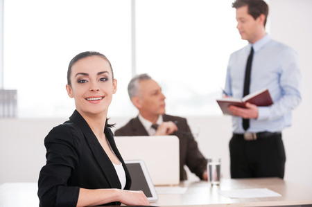 Happy to be a part of team. Attractive young woman in formalwear looking over shoulder and smiling while sitting at the table with two men talking on background  photo