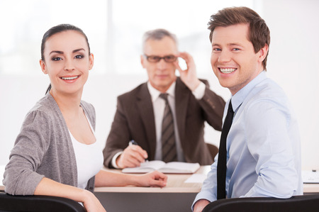 looking over shoulder: Successful business team. Confident business people looking at camera and smiling while sitting at the table together   Stock Photo