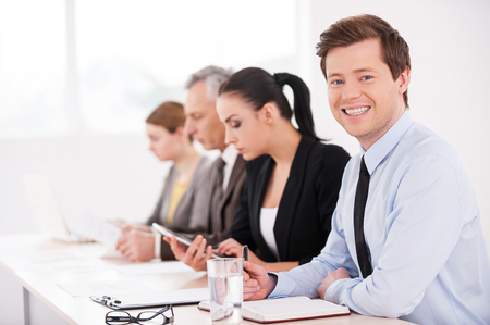 hair tie: Business seminar. Side view of confident business people sitting in a row at the table while one man looking at camera and smiling Stock Photo