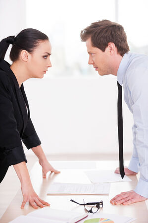 battle of the sexes: Business confrontation. Young man and woman in formalwear looking at each other and expressing negativity while standing face to face Stock Photo