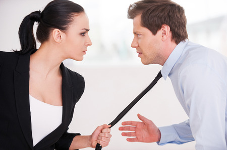battle of the sexes: Business conflict. Young man and woman in formalwear looking at each other and expressing negativity while woman grabbing the necktie of her opponent Stock Photo