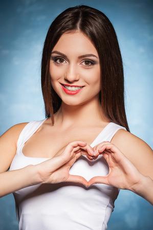 haciendo el amor: Te mostramos el amor. Señora joven sonriente haciendo una forma de corazón con las manos Foto de archivo