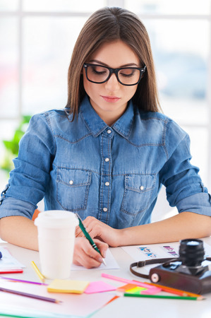 i pad: I love my job! Cheerful young businesswoman in casual wear writing something in note pad while sitting at his working place Stock Photo