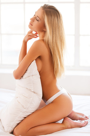 Shirtless beauty. Side view of beautiful young shirtless woman in only panties hugging a pillow and keeping eyes closed while sitting in bed photo