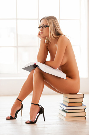 This book is too boring. Side view of beautiful young naked woman sitting on the book stack and holding a book photo