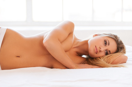 Beauty day dreaming. Beautiful young shirtless woman in panties lying in bed and covering breasts with hand photo
