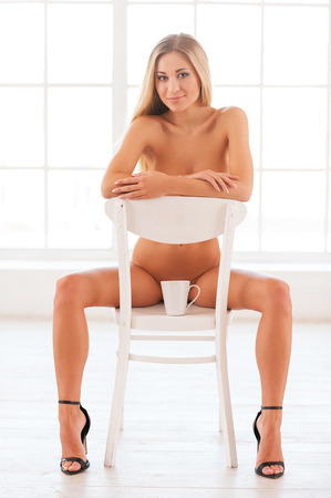 Beautiful seductress. Beautiful young naked woman in sitting on the chair and looking at camera  photo