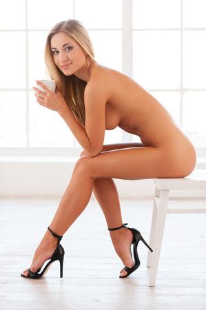 mujer desnuda sentada: Desnudo y feliz. Vista lateral de la mujer descubierta joven hermosa en zapatos de tacón alto sentado en la silla y sosteniendo una taza Foto de archivo