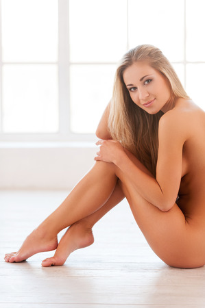 Naked beauty. Side view of beautiful young naked woman sitting on the floor and looking at camera photo