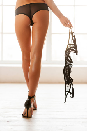 Taking off her bra. Cropped rear view image of beautiful young woman in black panties walking with bra in her hand photo