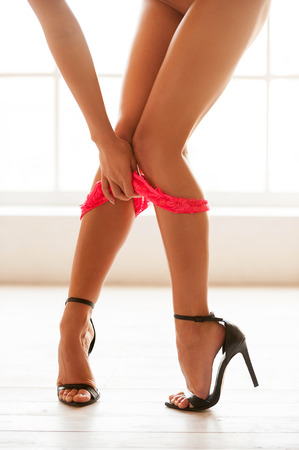 Taking her panties off. Cropped view image of beautiful woman in high heeled shoes taking off her panties  photo