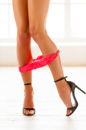 Taking the panties off. Cropped view image of beautiful woman in high heeled shoes taking off her panties  photo