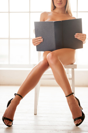 So exciting book! Cropped image of beautiful young naked woman sitting on the chair and reading a book photo