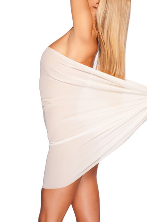 Beauty with smooth and healthy skin. Side view of beautiful young naked woman covering with white cloth while standing isolated on white photo