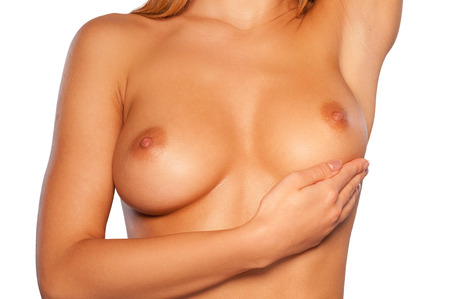 skin cancer: Examining breasts. Cropped image of young shirtless woman examining her breasts while standing isolated on white Stock Photo