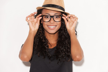 Funky style beauty. Portrait of beautiful young African woman in glasses and funky hat adjusting her glasses and smiling while standing against white background Reklamní fotografie