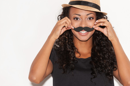 Having fun with face mustache. Cheerful young African woman in funky hat holding fake mustache on her face and looking at camera while standing against white background photo