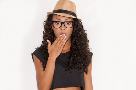 No way! Surprised young African woman in glasses and funky hat covering mouth with hand and looking at camera while standing against white background photo