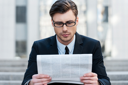 handcarves: Morning news. A young businessman reading a newspaper outdoors