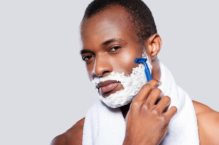 Man shaving. Handsome shirtless African man shaving his face and looking at camera while standing against grey background Stock Photo